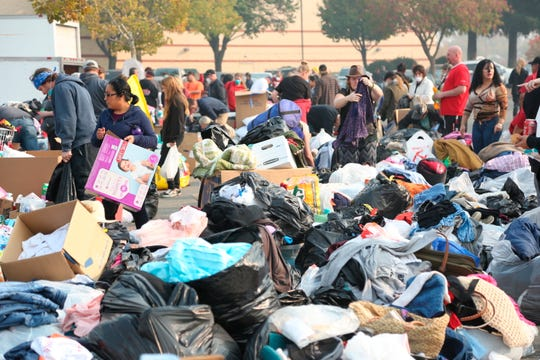 Piles of donated items fill up a section of parking lot surrounding the Chico Walmart where a tent city of Camp Fire evacuees has formed. Many of the evacuees have lost their homes to the Camp Fire, leaving an estimated 10,000 homeless.