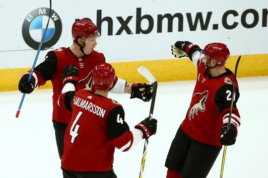 Coyotes center Derek Stepan (21) celebrates his goal against the Golden Knights with defensemen Niklas Hjalmarsson (4) and Jakob Chychrun, left, during the first period of a game Nov. 21 at Gila River Arena.
