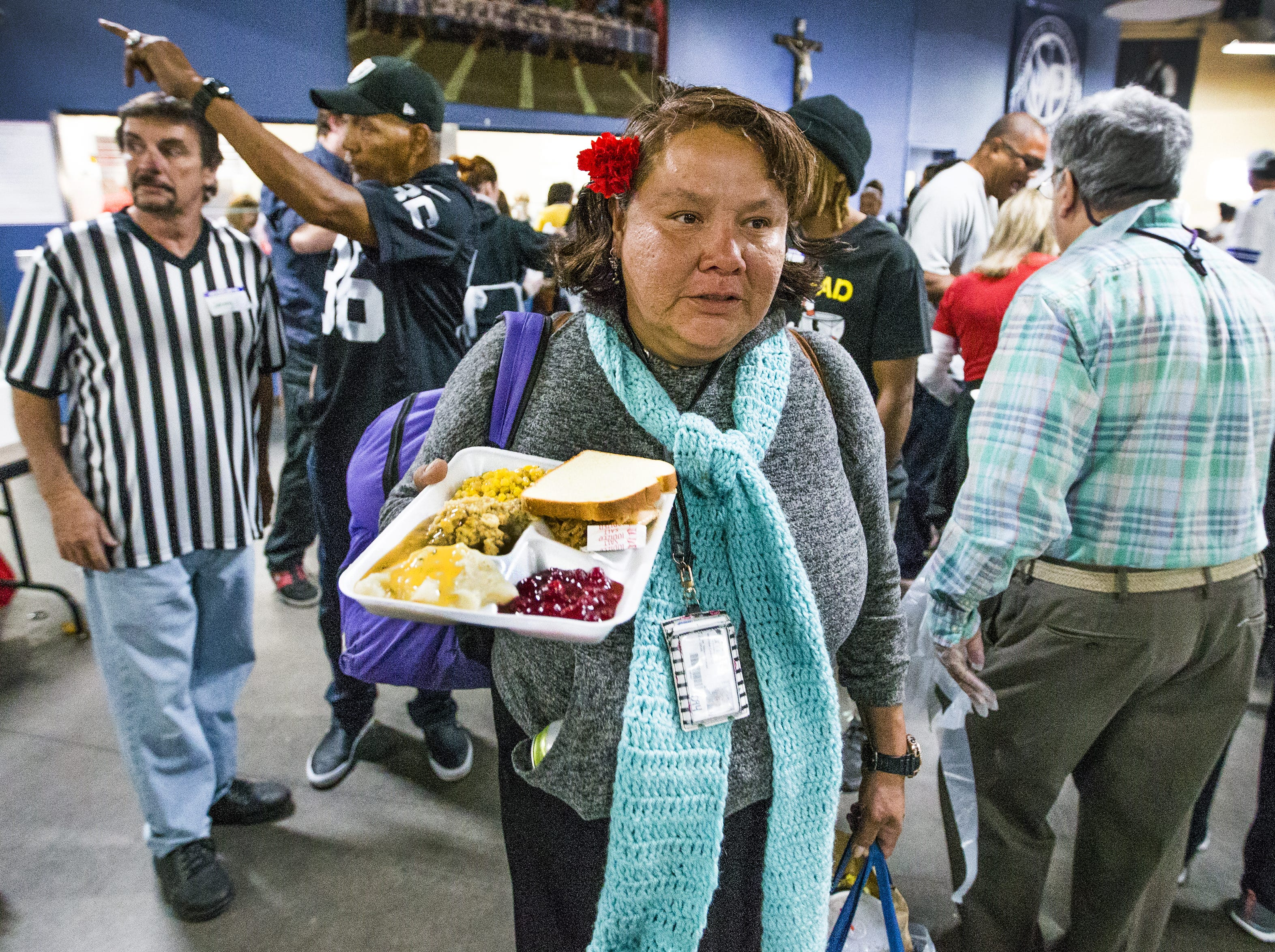 Natasha Claw carries her plate to a table to enjoy a Thanksgiving Day meal served by volunteers at the St. Vincent de Paul Society Human Services Campus Dining Room in Phoenix, Thursday, November 22, 2018.   Turkey, mashed potatoes and pumpkin pie were on the menu.