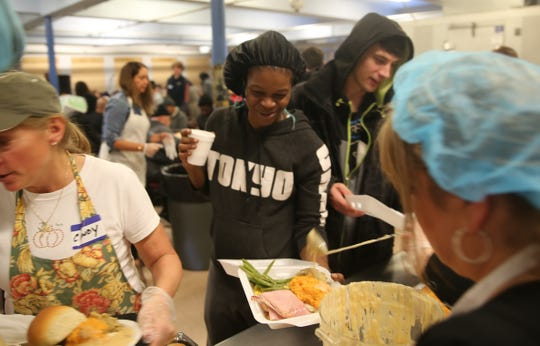 Latanya Floyd, 40, picks up a meal on Thanksgiving 2018 during the annual Eileen Hickey Holiday Dinner held at The Lunch Box in the Family Partnership Center.