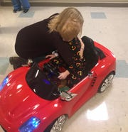 Tiffany Shane hugs 6-year-old son Logan, who sits in the toy electric car he drove himself to his operating room, before surgery on Tuesday, Nov. 20, 2018, at York Hospital.