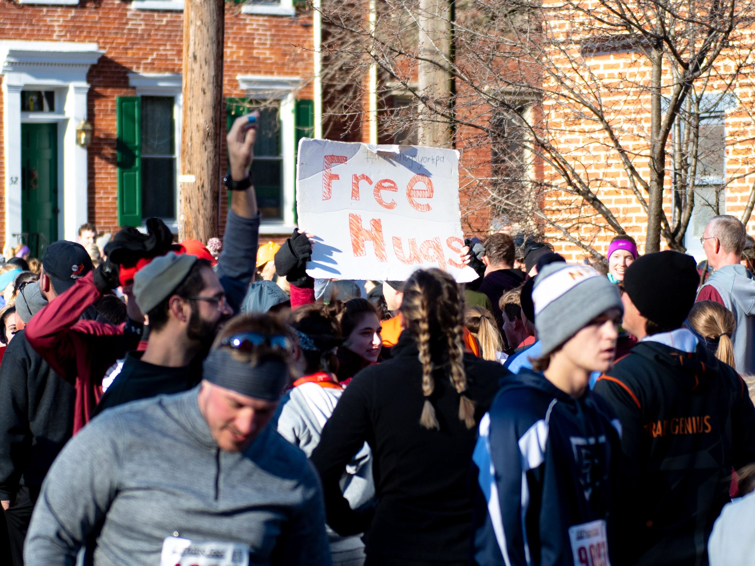 People hold up signs during the 22nd Annual Turkey Trot 5K, on Thanksgiving Day, November 22, 2018.