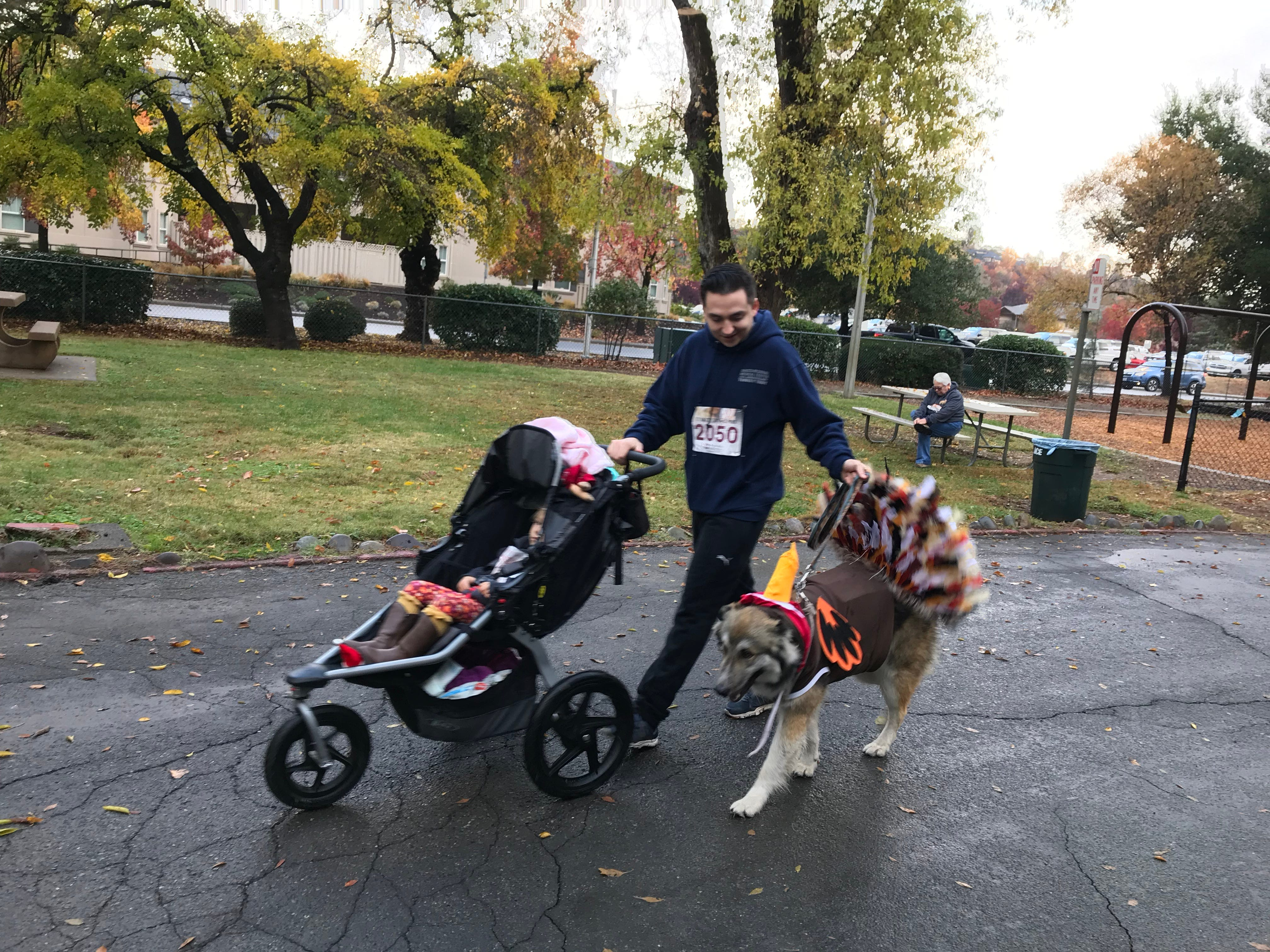 Moose the dog dressed as a turkey and his owner, Zakari Velenzuela. Jordan rides in the stroller.