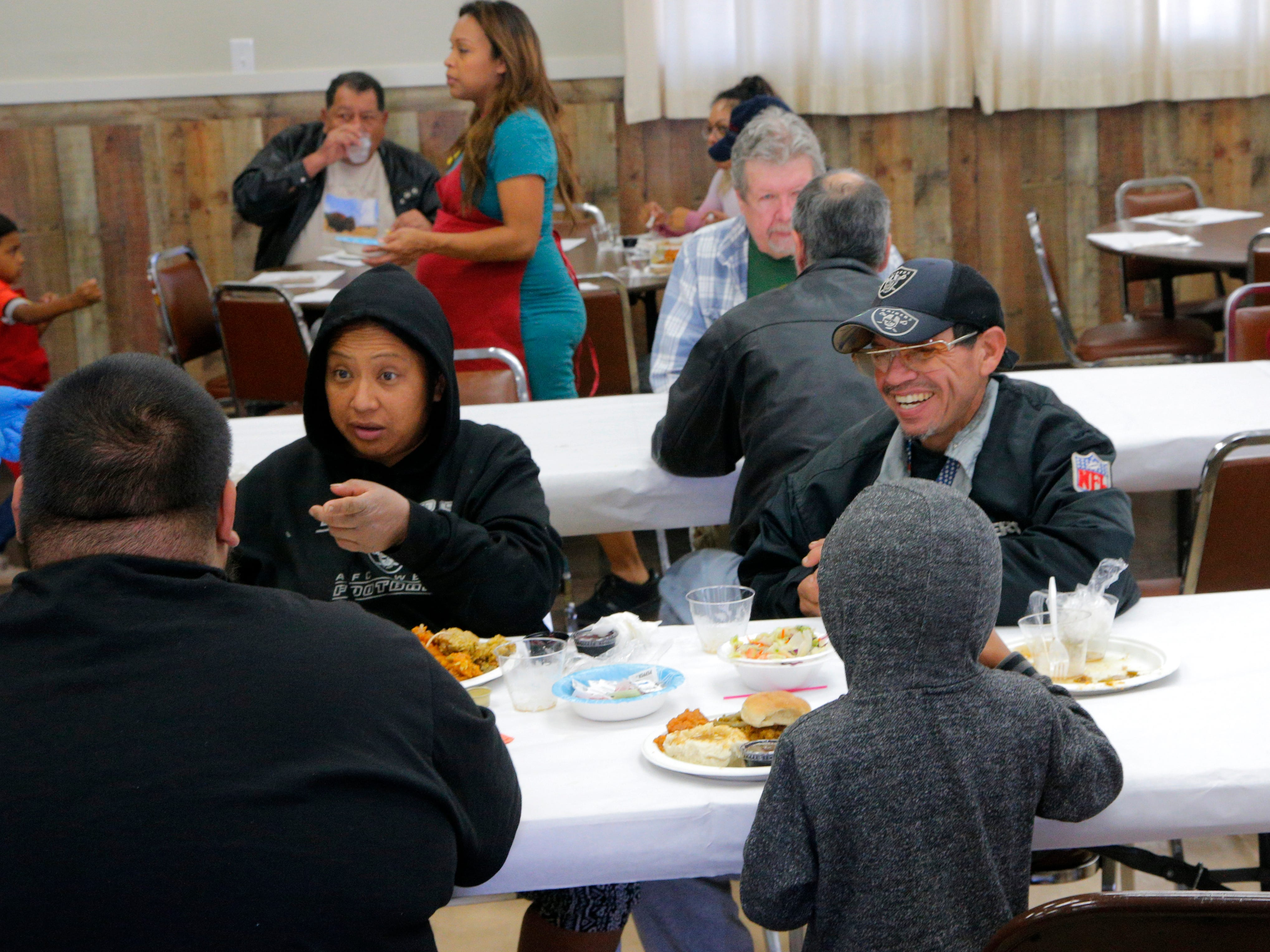 Lenora Gabot (left) speaks with her sons Jessie Orozco, 25, and Zephaniah Gabot, 6, on Thanksgiving during the American Legion Post 31's free feast.