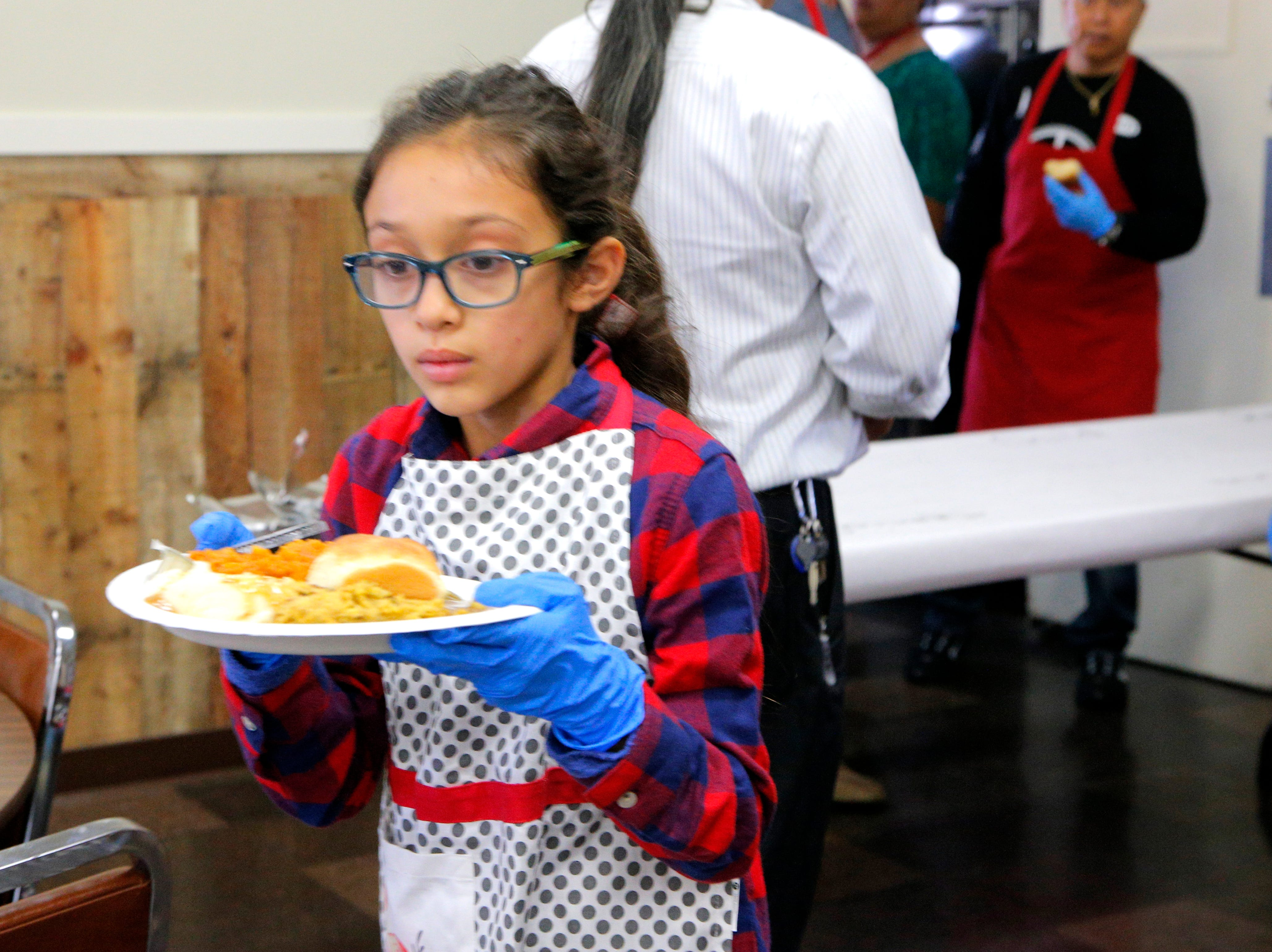 Juliana Jimenez, 8, serves a Thanksgiving meal at the American Legion Post 31.