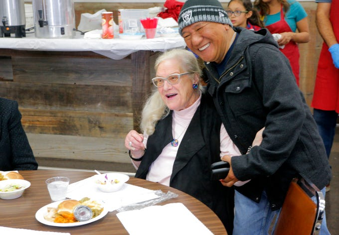 Rolando Acidera hugs his friend Ursula Pherigo Thursday during the American Legion Post 31's Thanksgiving Day feast, which was free and open to the public.
