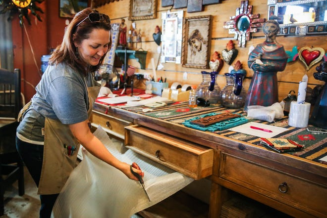 Sadie Cartwright wraps an item for a customer Saturday, Nov. 17, 2018, at Casa Decor.