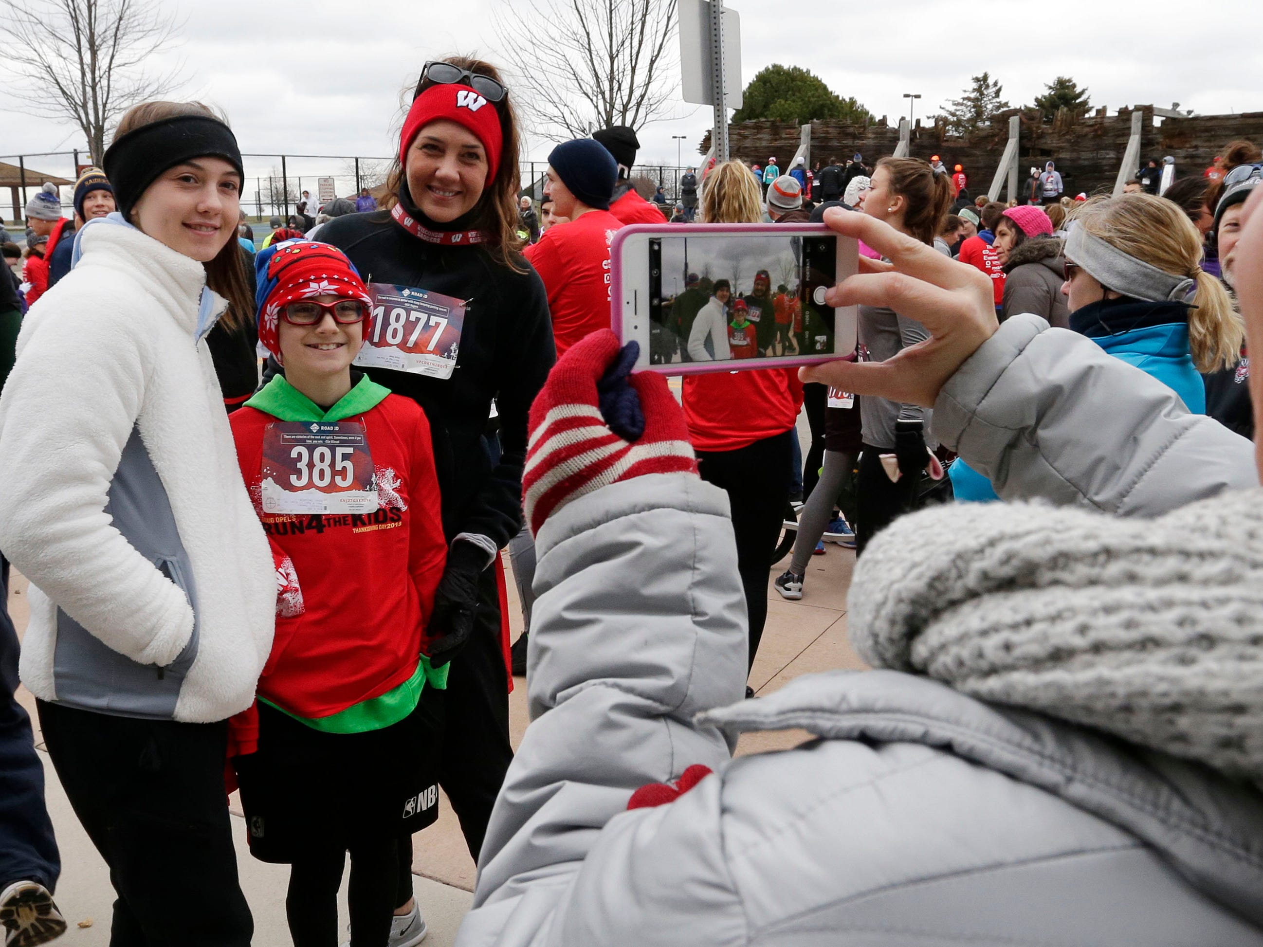 Sydney Scheibl, left, poses with her brother Sam, middle, and with Angela, right, before the Doug Opel Run for the Kids, Thursday, November 22, 2018, in Sheboygan, Wis.
