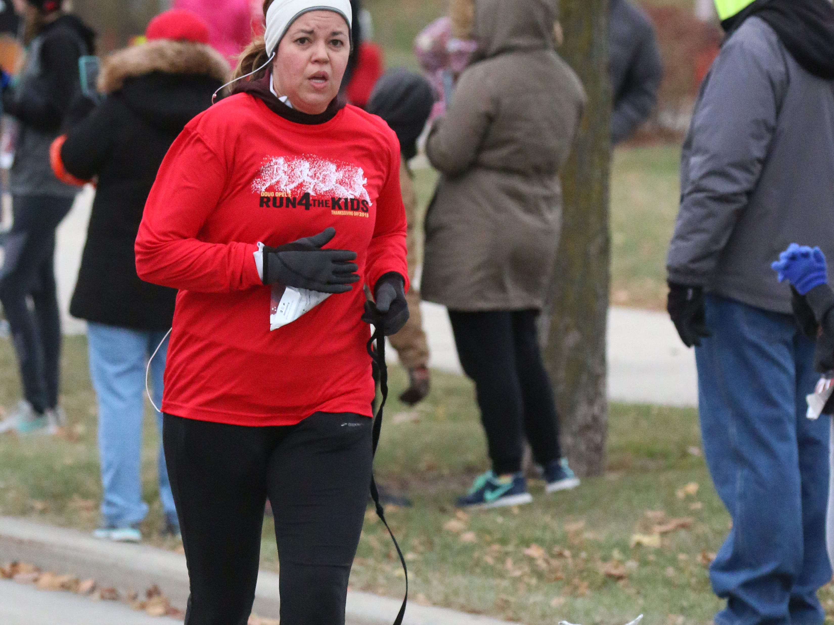 Carla Yancy of Sheboygan runs with her dog Finn during the Doug Opel Run for the Kids, Thursday, November 22, 2018, in Sheboygan, Wis.