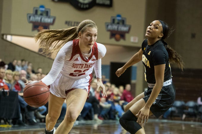 USD's Chloe Lamb (22) dribbles the ball past a Wichita State player at the Sanford Pentagon in Sioux Falls, S.D., Wednesday, Nov. 21, 2018.