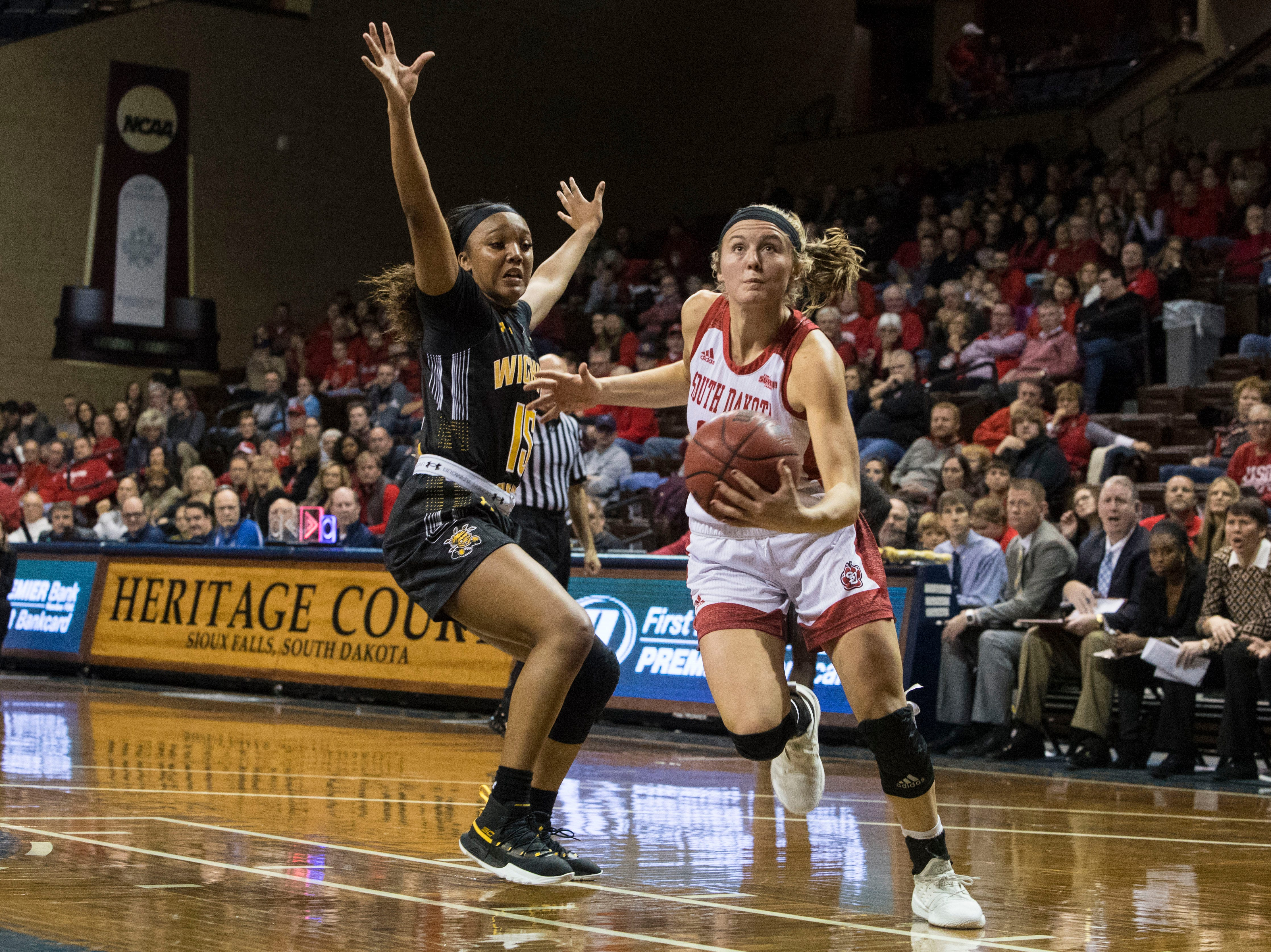 USD's Allison Arens (10) dribbles the ball past a Wichita State player at the Sanford Pentagon in Sioux Falls, S.D., Wednesday, Nov. 21, 2018.