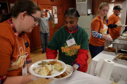 Volunteers Sister Nelson, left and Tracy E. Mathews serve plates of food during the Annual Community Thanksgiving Celebration at the American Legion Post 13 on Lake Ella Drive in Tallahassee, Fla. Thursday, Nov. 22, 2018.