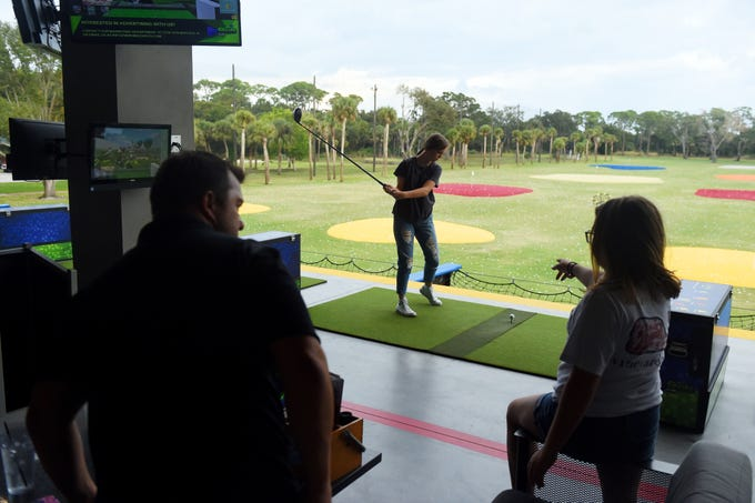 Celeste Lott, 14, of Fort Pierce, goes into her backswing as she prepares to hit a golf ball from the upper deck of tee-boxes at BigShots Golf in Vero Beach as her father, Joe (left) and sisters Mattie (right) and Mary-Alice Lott (not pictured) look on. The foursome decided to have a family day while the weather was nice and the girls were out of school for the Thanksgiving holiday. BigShots Golf is situated on 10-acres of land at 3456 U.S. 1 and features an upper and lower deck of tee-boxes, a full-service restaurant, two bars and a private event space.