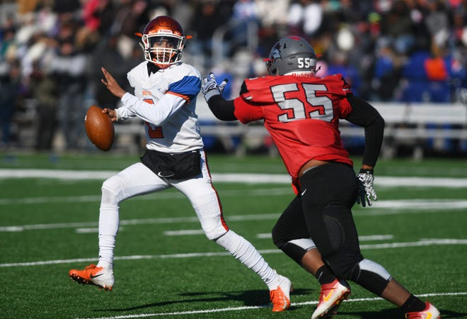 Millville's QB Eddie Jamison is chased by Jhamir Malloy during a game against Vineland at Gittone Stadium on Thanksgiving Day.