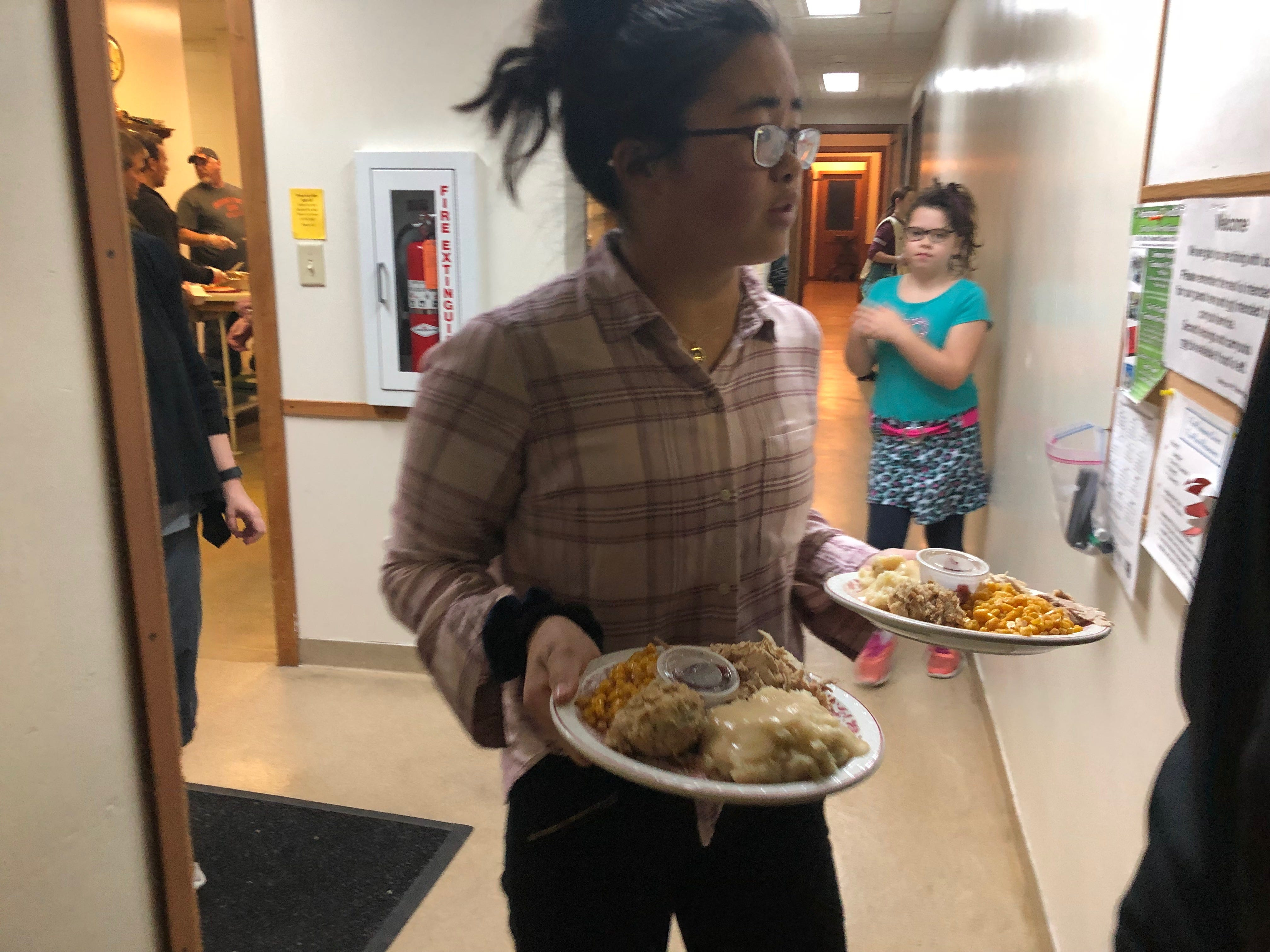 A volunteer carries plates of Thanksgiving dinner out to community members at First Presbyterian Church on Nov. 22.