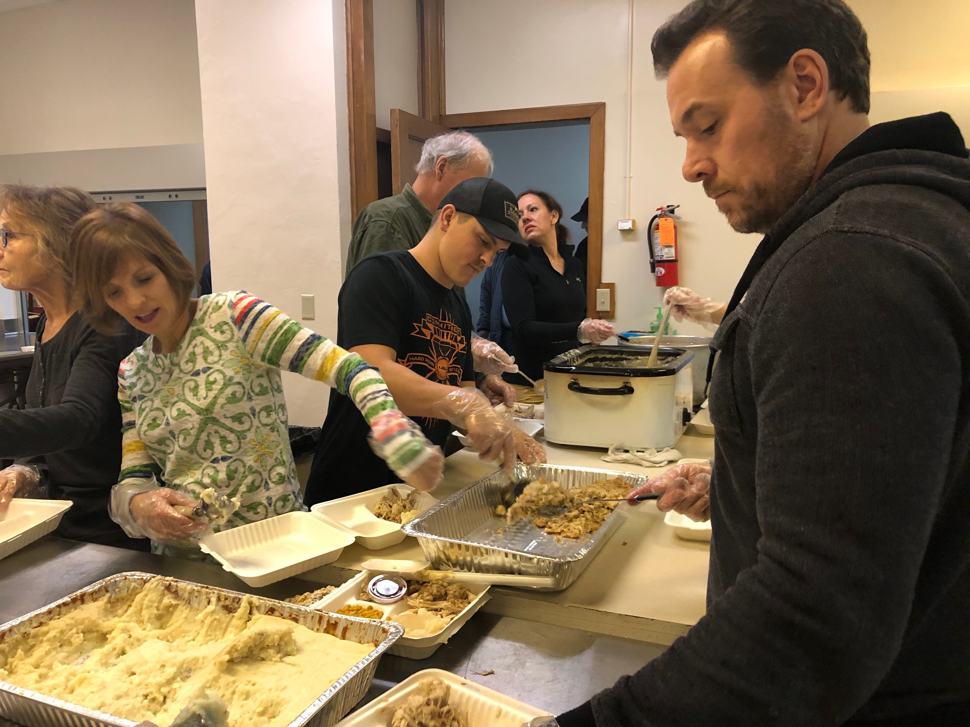 Volunteers scoop out Thanksgivng foods at First Presbyterian Church on Nov. 22.