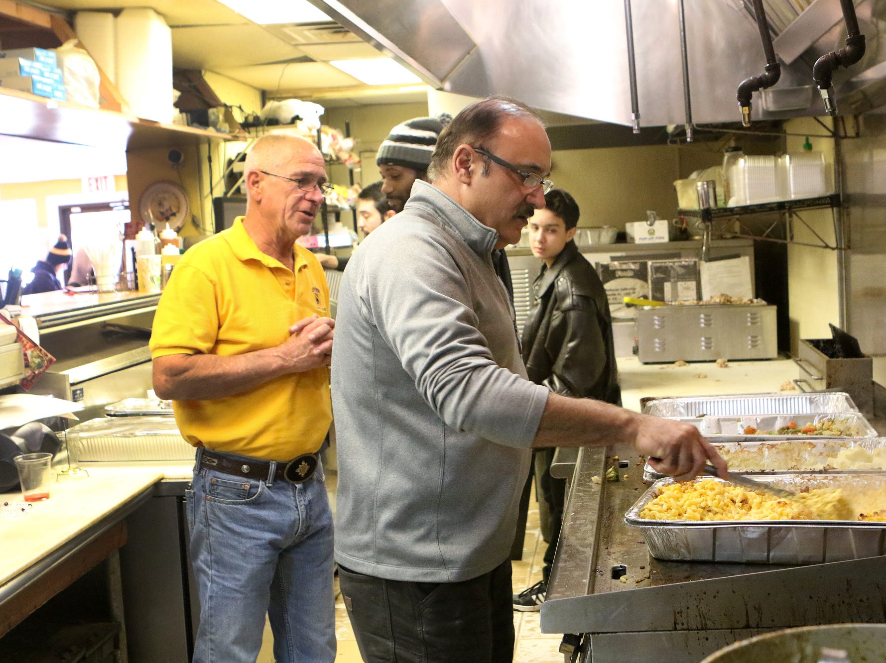 Simaron Pizza & Steak Shop owner Edmound Yousef Khanian adds gravy to a dinner-to-go Thursday while Jerry Lawrence from the Dover Lions Club looks on. Khanian opened up his Dover restaurant on Thanksgiving Day to feed those who couldn't afford dinner or who were alone on the holiday.