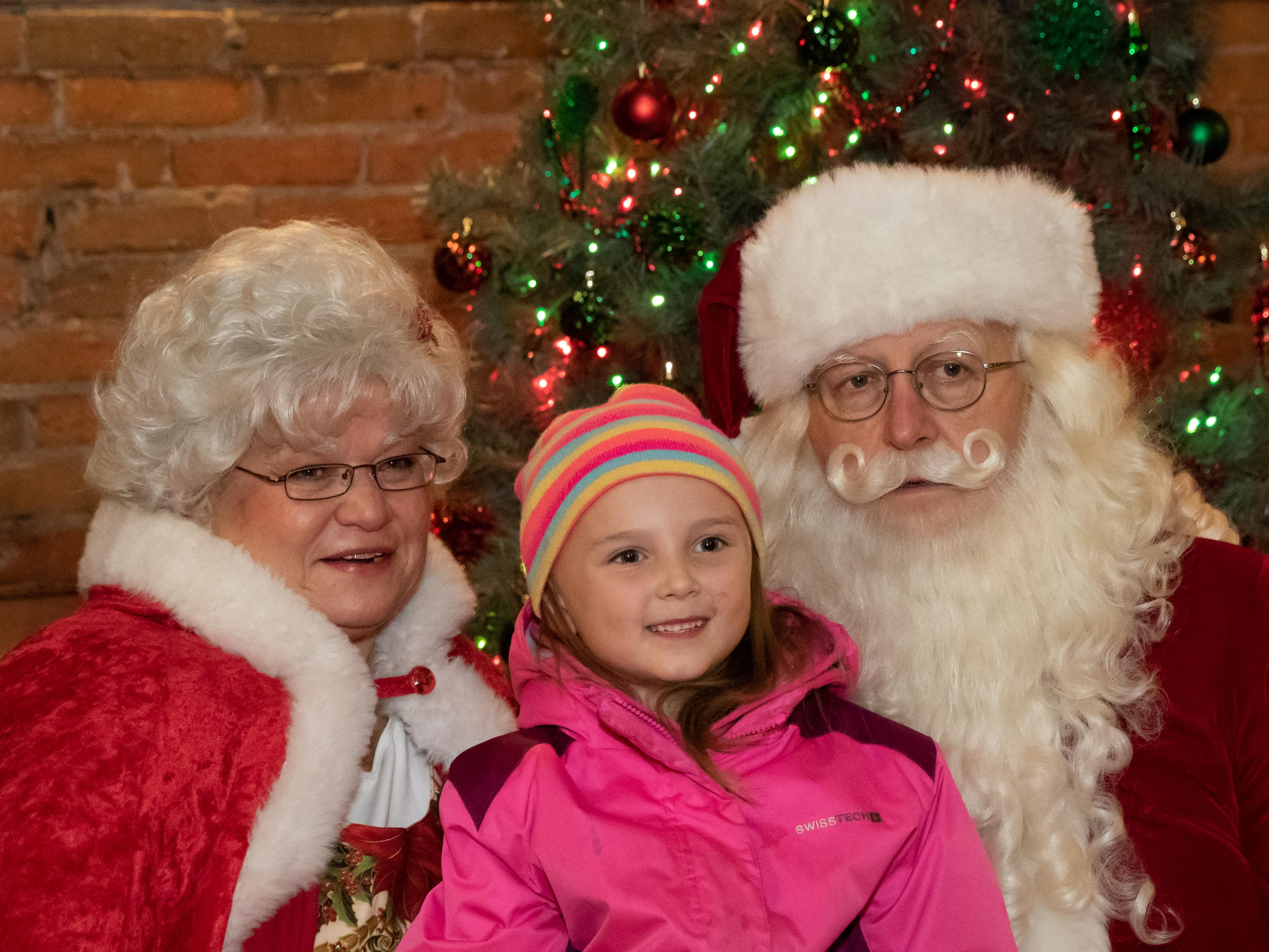 A young girl visits with Santa and Mrs. Claus following the Rekindle the Season holiday parade on Wednesday, Nov. 21, 2018, in downtown Wisconsin Rapids.