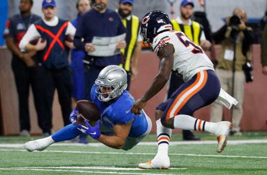 Lions fullback Nick Bellore makes a catch as Bears inside linebacker Danny Trevathan (59) defends.