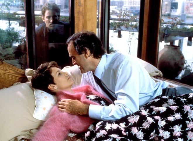 "Kevin Kline, peers in at Jamie Lee Curtis and John Cleese in the 1988 film ""A FISH CALLED WANDA."""