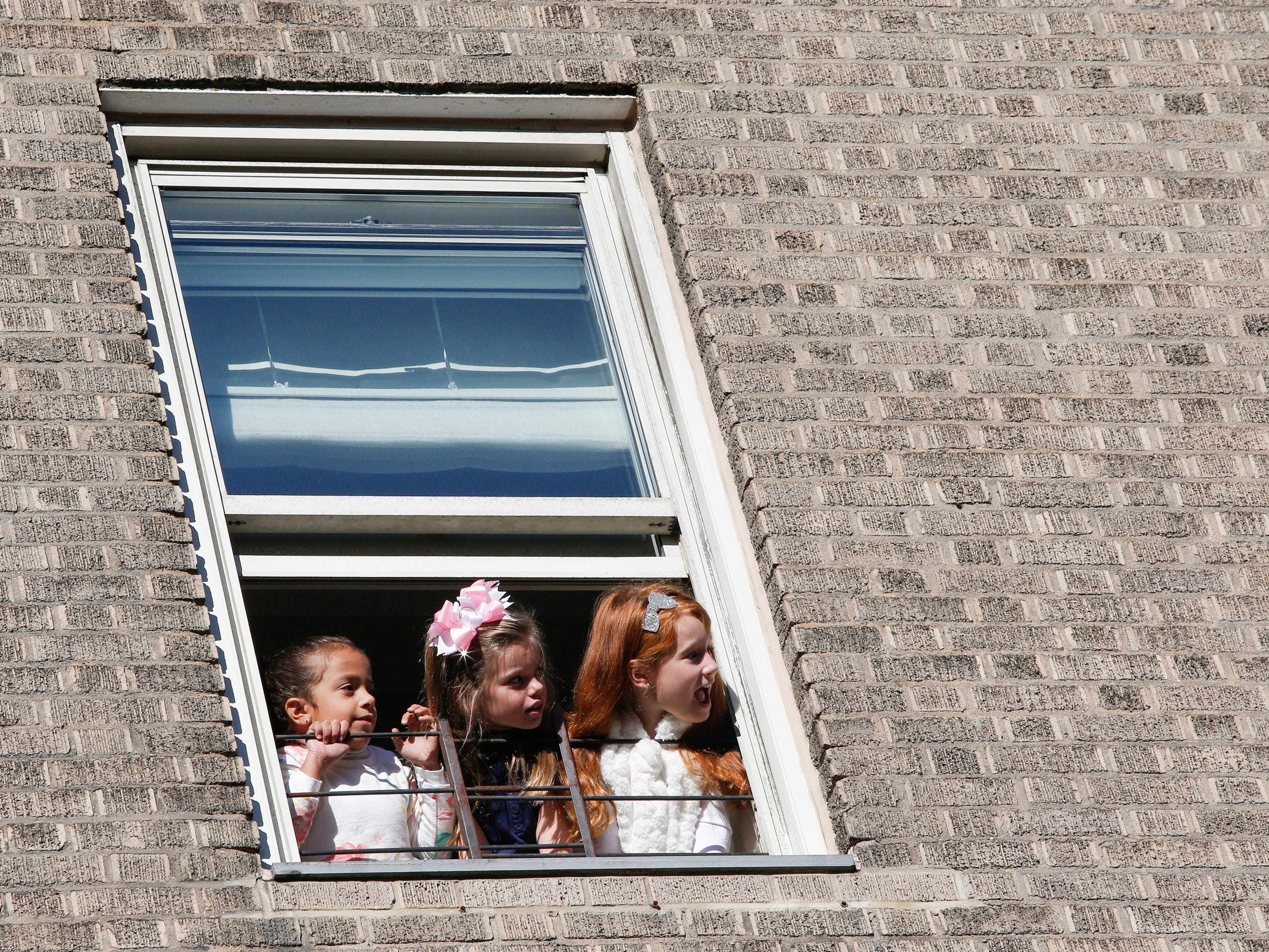 Children look at balloons from a window during the 92nd annual Macy's Thanksgiving Day Parade in New York, Thursday, Nov. 22, 2018.