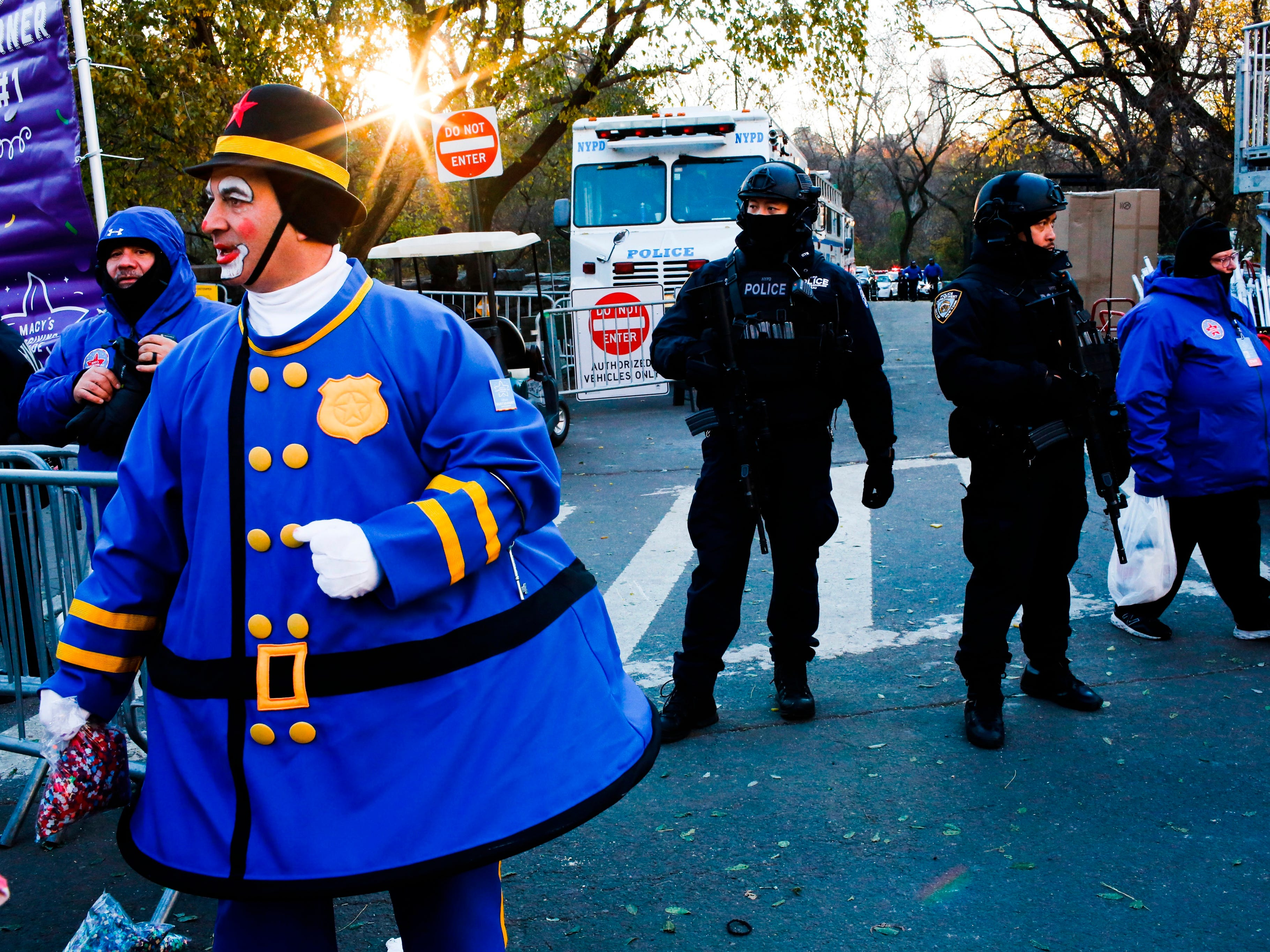 Police and people in costume take a position along the route before the start of the 92nd annual Macy's Thanksgiving Day Parade in New York, Thursday, Nov. 22, 2018.