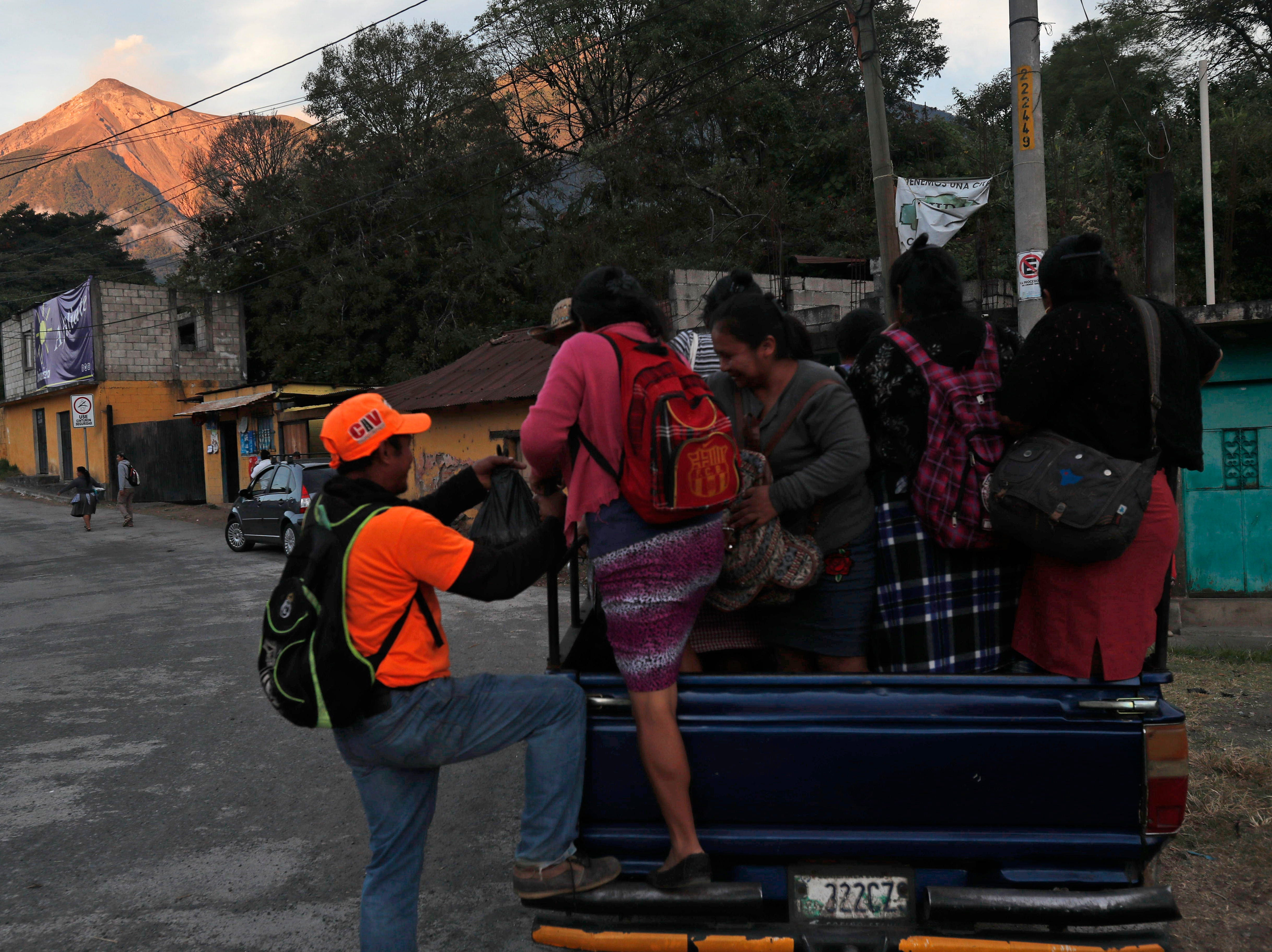 Residents get in a truck as they leave their homes to go to work in coffee fields, backdropped by the Volcan de Fuego, or Volcano of Fire, in San Juan Alotenango, Guatemala, Tuesday, Nov. 20, 2018. The volcanology institute reported that the eruption of the volcano ended on Monday evening, as families who heeded the call of disaster coordination authorities to evacuate 10 communities, started returning home.