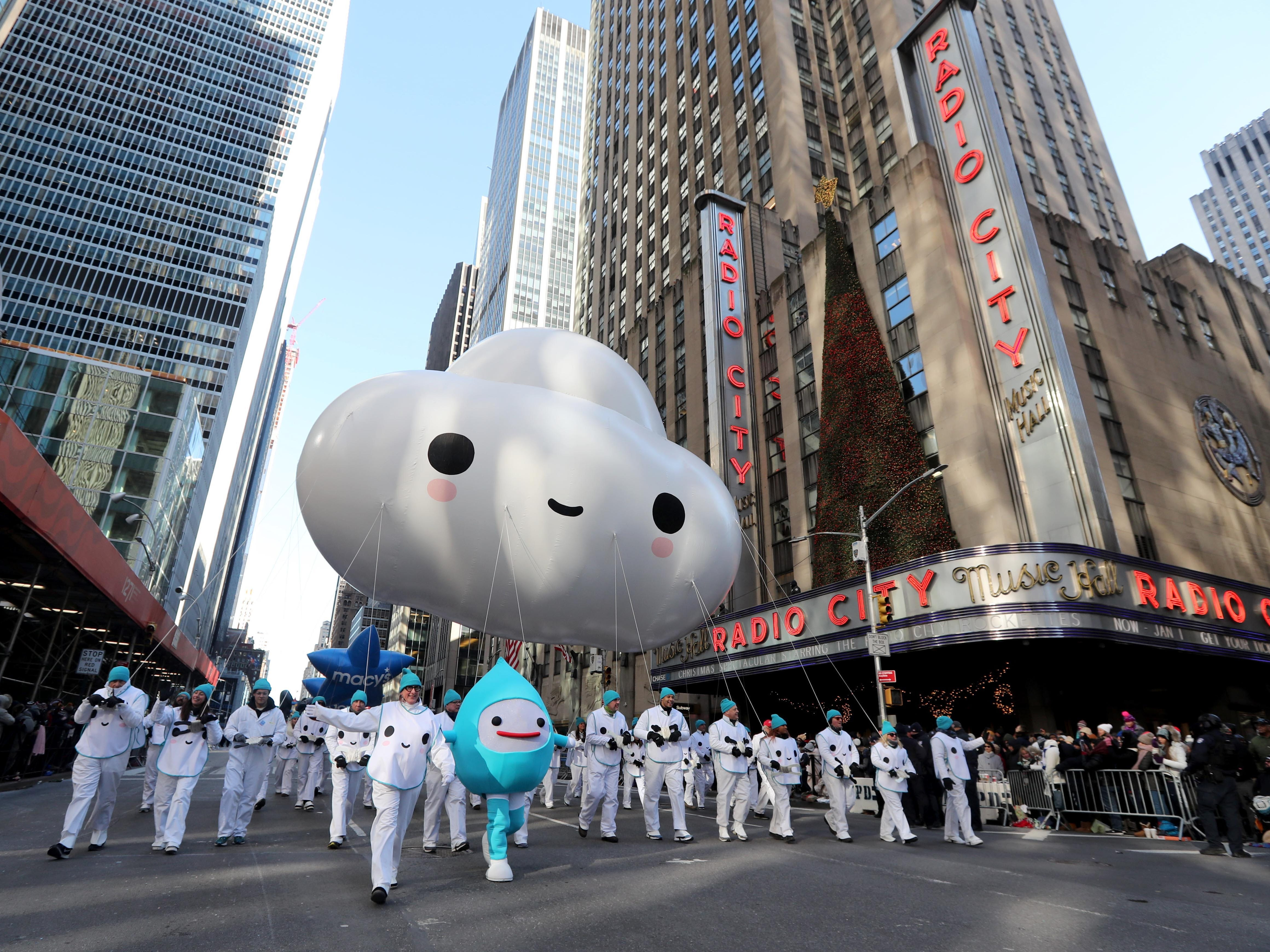 The Little Cloud balloon makes its way past Radio City Music Hall on 6th Ave. in New York during the annual Macy's Thanksgiving Day Parade, Nov. 22, 2018.