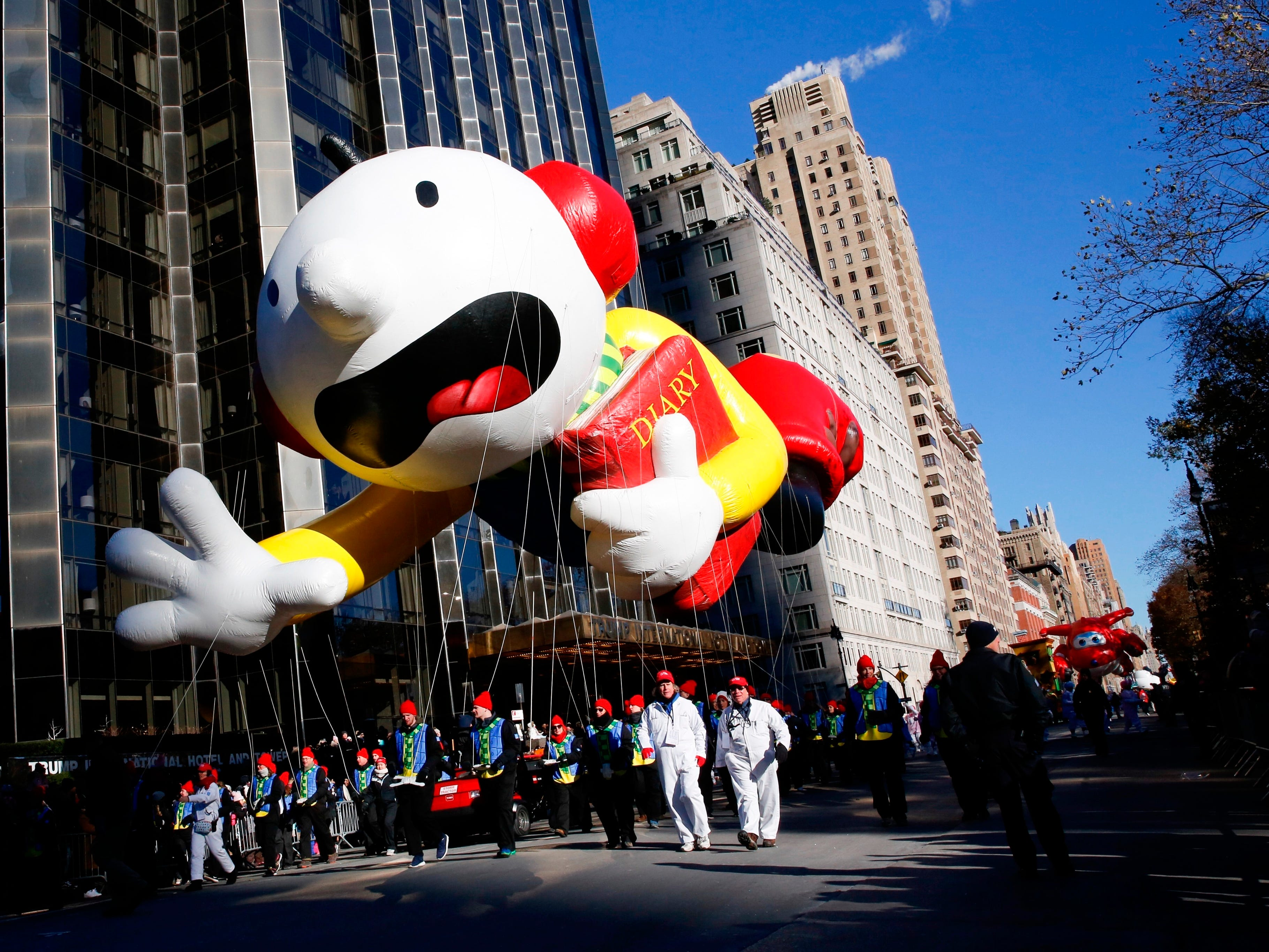 "Greg Heffley from the ""Diary of a Wimpy Kid"" series balloon passes by windows of a building on Central Park West during the 92nd annual Macy's Thanksgiving Day Parade in New York, Thursday, Nov. 22, 2018."