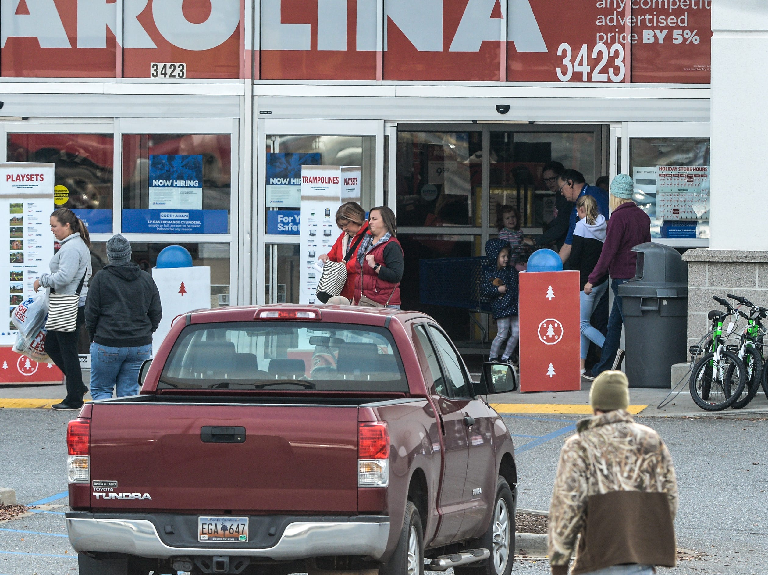 Customers go in and out of Academy Sports in Anderson during Black Friday sales on Friday, November 23, 2018.