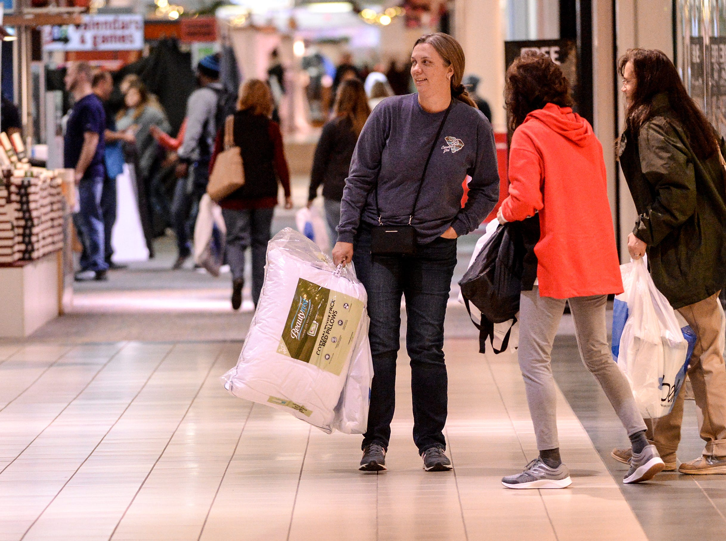 Customers Leandra Robinson, left, of Moncks Corner holds a bag with pillows after shopping in the Anderson Mall for Black Friday sales items in Anderson on Friday, November 23, 2018.