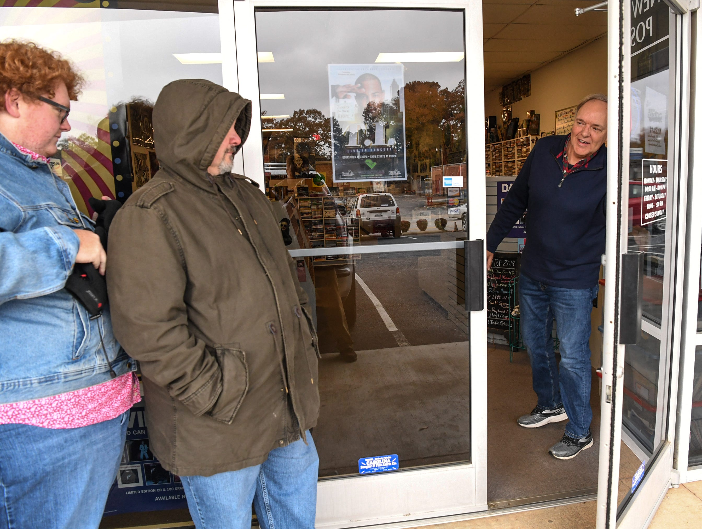 Owner Mark Hembree, right, opens the door for customers Coleman Grimes, left, and his father Robbie Grimes, middle, of Powdersville, in line at Rainbow Records for Record Store Day on Black Friday in Anderson on Friday, November 23, 2018.