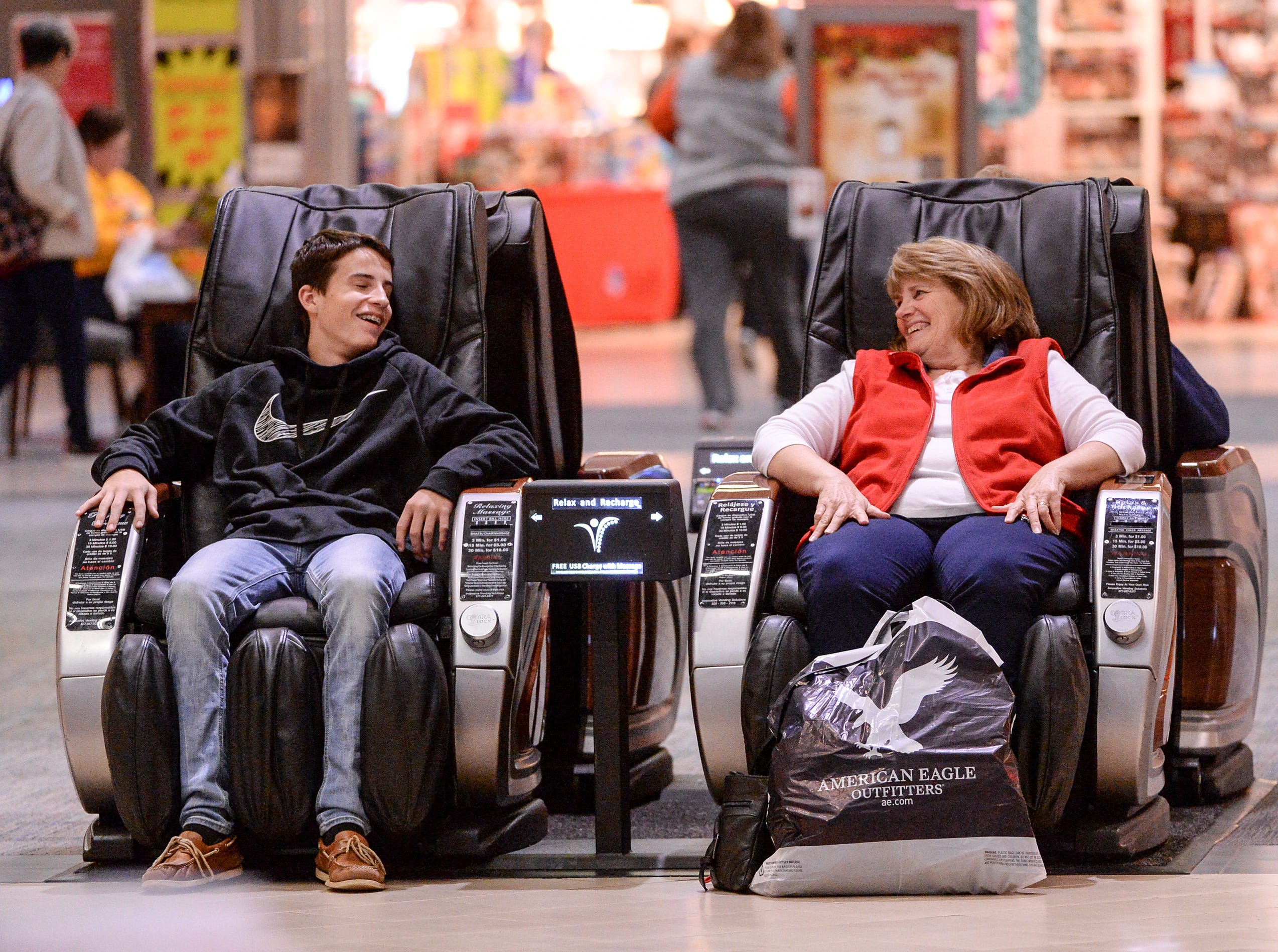 Andrew Dickerson, left, and Carol Rutledge, both of Belton, relax in massage chairs after shopping in the Anderson Mall for Black Friday sales items in Anderson on Friday, November 23, 2018.