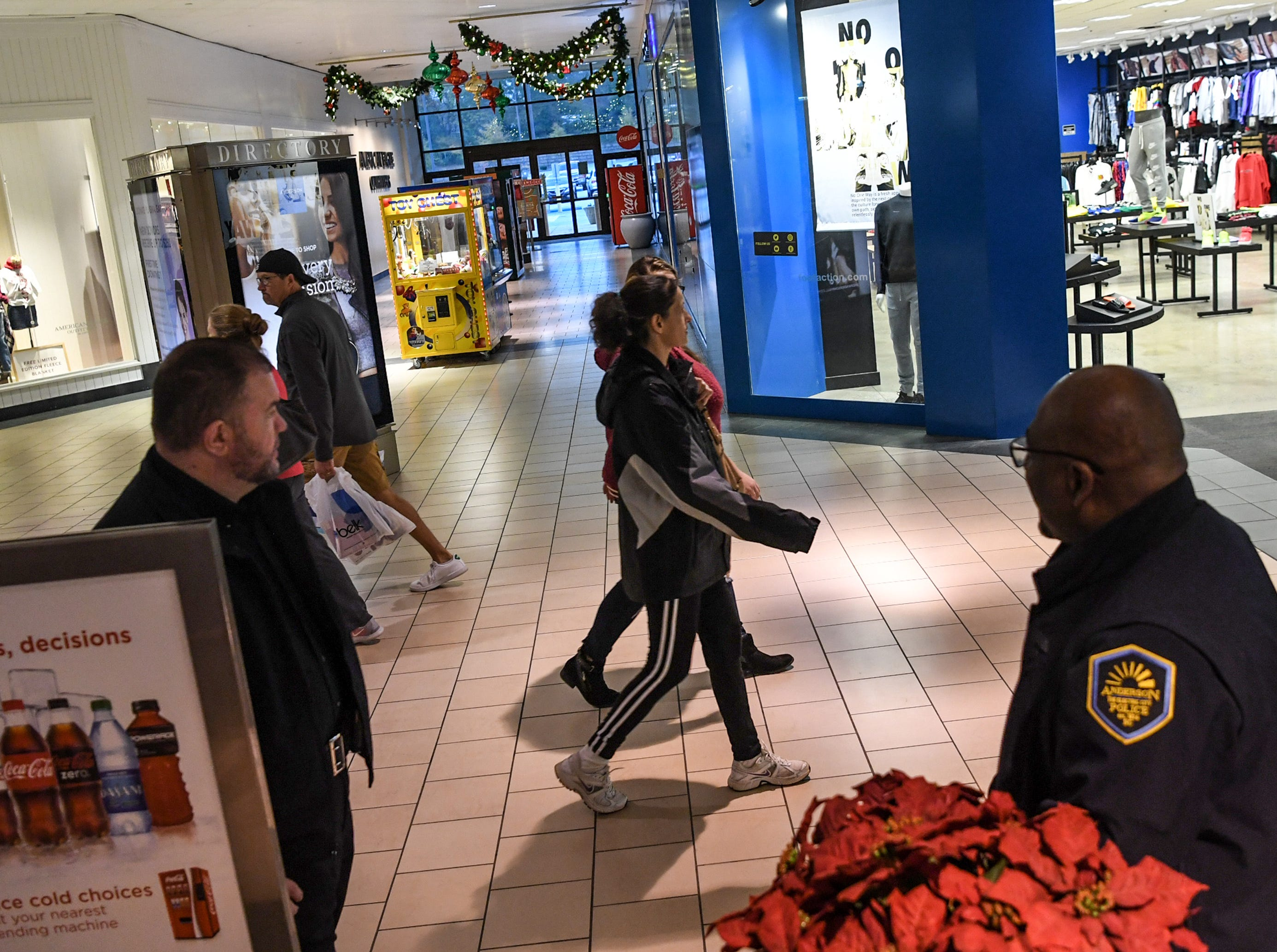Shoppers walk by Anderson police during Black Friday sales in Anderson on Friday, November 23, 2018.
