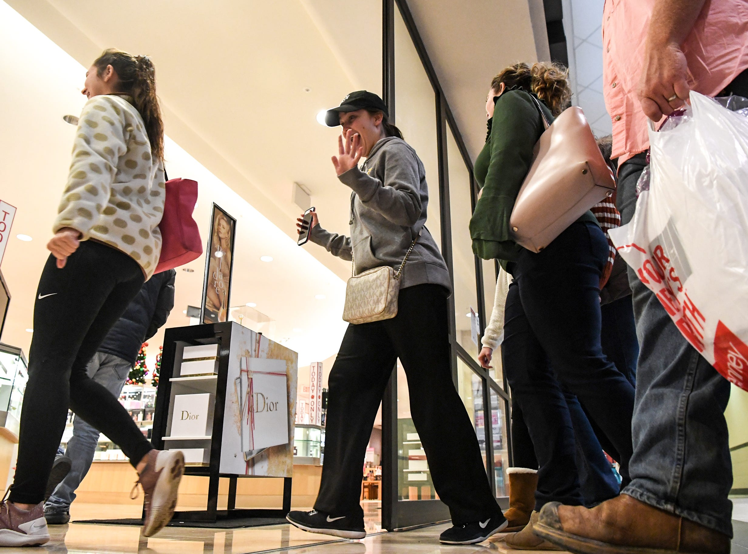 Customers walk through doors opening at Dillard's during Black Friday sales at the Anderson Mall in Anderson on Friday, November 23, 2018.
