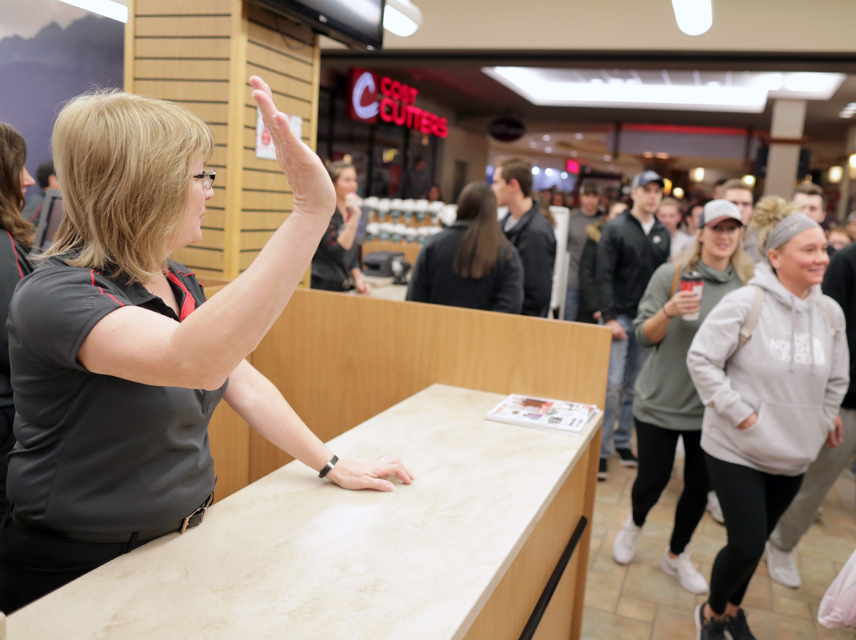 Dawn Hendrickson waves to shoppers looking for Black Friday deals at Scheels on Friday, Nov. 23, 2018 in Grand Chute, Wis