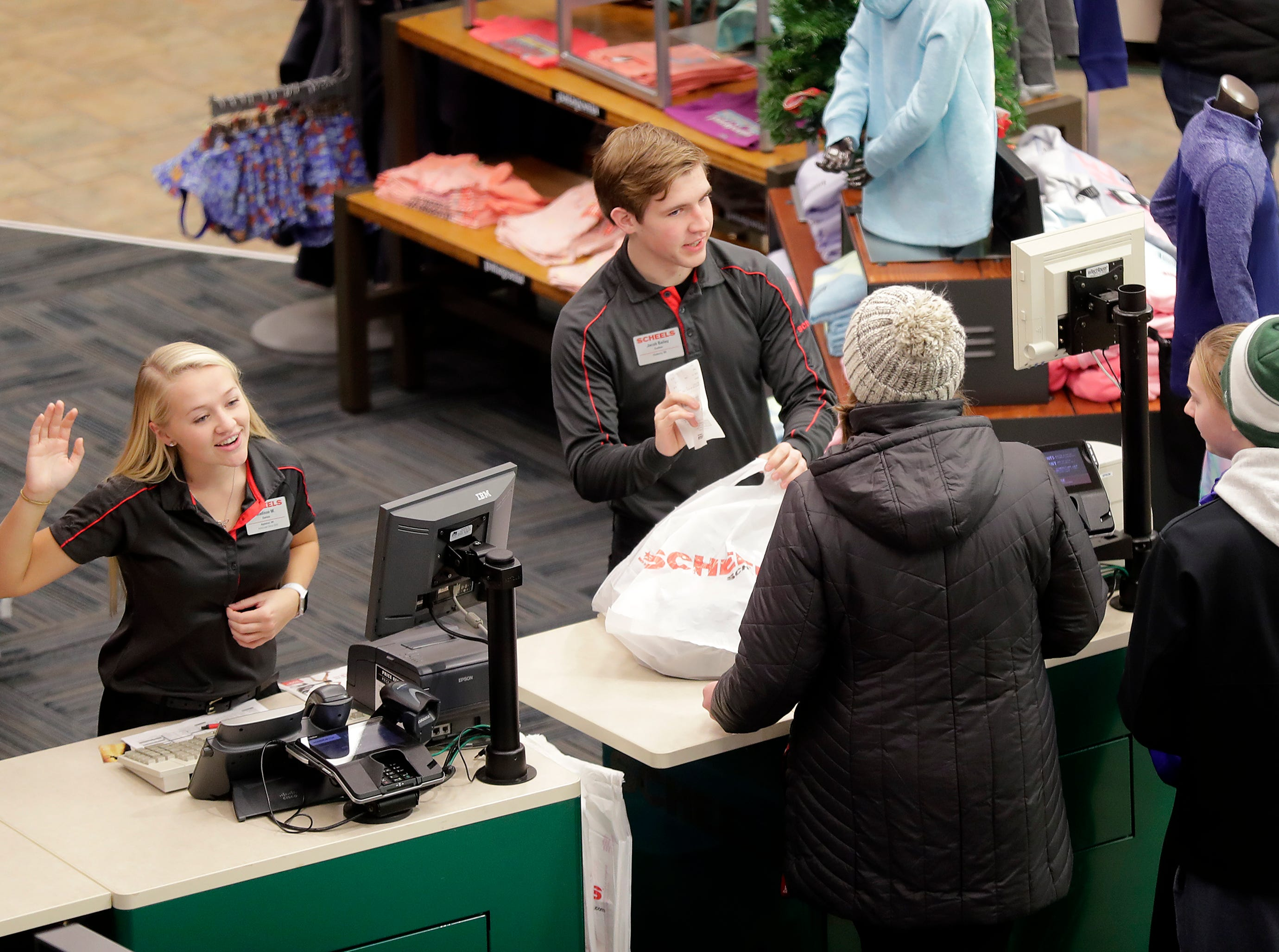 Madison Maloney, left, and Jacob Bailey work the registers as shoppers looking for Black Friday deals at Scheels on Friday, Nov. 23, 2018 in Grand Chute, Wis
