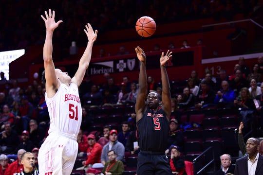 Rutgers forward Eugene Omoruyi shoots over Boston University's Max Mahoney, a Ridge H.S. grad.