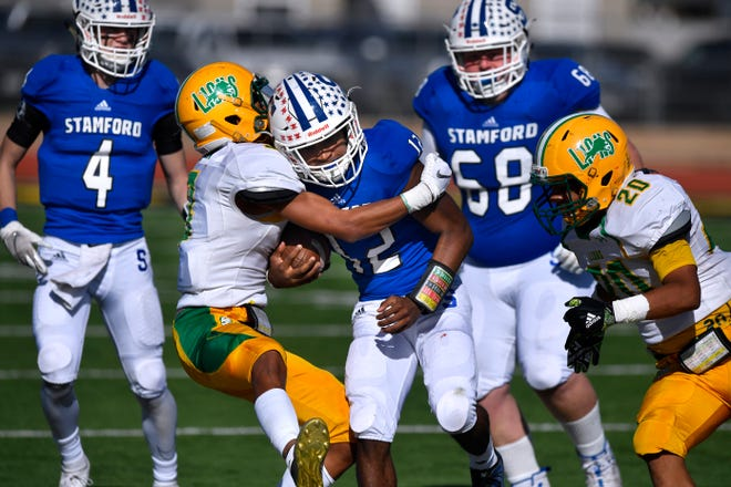 Stamford running back Tre Mitchell is wrapped up by New Deal defensive back D.K. Blaylock during Friday's playoff game in Snyder. New Deal won the game, 64-6.