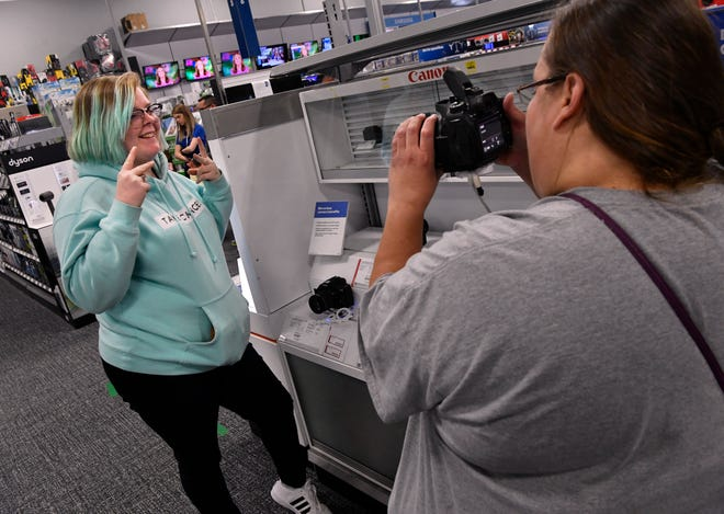 Bethany Ingle poses for her aunt Jeannie TenCate during while shopping for cameras at Best Buy in Abilene Friday. The pair came from Moran to do a little Black Friday shopping.