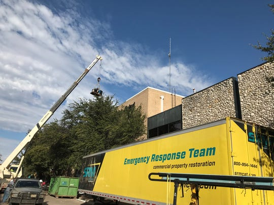 A crane lowers a generator used on the roof of the Reporter-News at the location of the Nov. 15 fire, the building's utility room. Good weather has assisted crews in cleanup and the assessment of damages to the building at North First and Cypress streets.