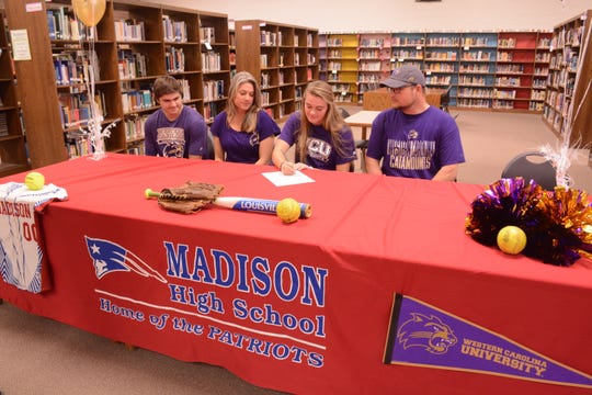 Savannah Rice signing with Western Carolina University as her parents and brother look on.
