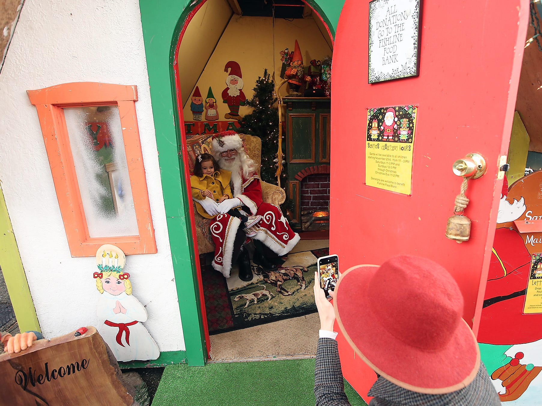 Nordic Father Christmas, played by Danny Fritts, holds Luna Junker, 3, of Bainbridge Island, on his lap while mom Hana snaps a photo on Friday, November 23, 2018.