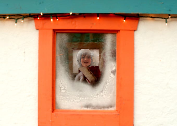 Clark Rasmussen, 6, peeks into the window of Nordic Father Christmas's hut in downtown Poulsbo on Friday, November 23, 2018. Clark was too shy to talk to Nordic Father Christmas, played by Danny Fritts, so he stuck with peeking into the windows and waving. Those outgoing enough to visit Nordic Father Christmas in his house can head to downtown Poulsbo 11 to 3 on Saturdays and 12 to 3 on Sundays and donations benefit Fishline.
