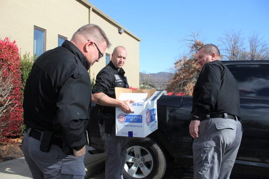 Black Mountain police officer Jon McDonald loads a box of mostly non-perishable food items into a truck outside of the station as chief Shawn Freeman opens the back door and Lieutenant Joe Kidd looks on. The trio were joined by town manager Josh Harrold and mayor Don Collins as they delivered the box to Mary Fender.