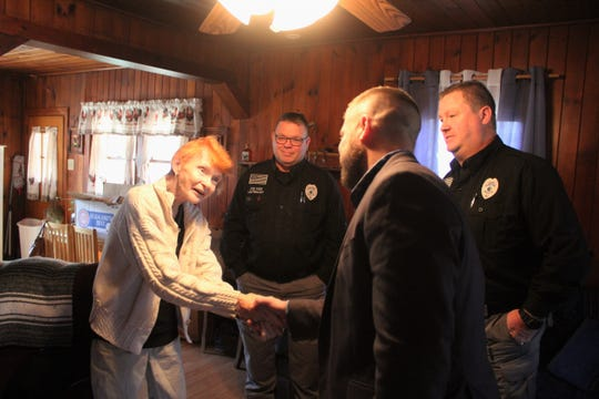 Mary Fender shakes Josh Harrold's hand on Nov. 20, when the town manager, mayor, chief of police and two other officers from the department dropped off a box of food for the holidays.
