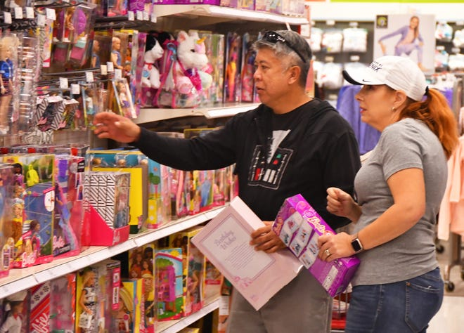 Richard and Tammy Cheng of Melbourne were having a hard time deciding on the correct Barbie for a four year old at the Viera Super Target Friday. Shoppers were out early Friday morning shopping for door busters and Black Friday deals.