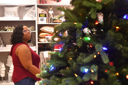 In a file photo, Jennifer Snyder looks for a deal on a Christmas tree on Black Friday at JCPenney at Merritt Square Mall.