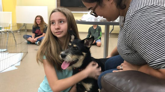 "Marissa Sotello, 13, and her mother, Larissa Cheek, play with Bella during  ""Cats, Canines and Coffee"" at the Gulf Coast Humane Society on Friday, Nov. 23, 2018."