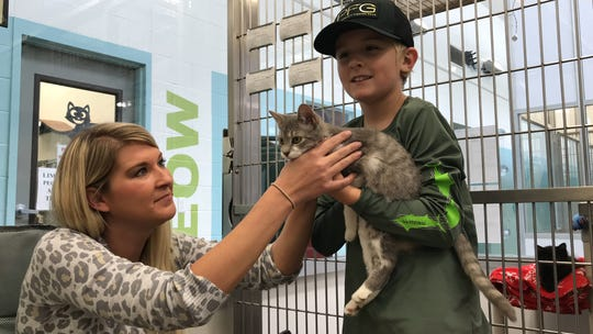 """Jordan Crow and her son, Maddox Clarke, 9, pet Brisco during """"Cats, Canines and Coffee"""" at the Gulf Coast Humane Society on Friday,  Nov. 23, 2018."""